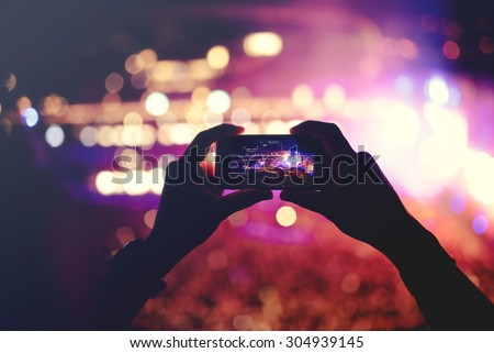 Silhouette of hands recording videos at music concert. Pop music concert with lights, smoke and lots of people - stock photo