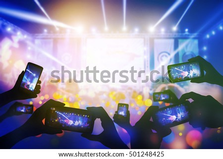 Silhouette of hands using smart phone to take pictures and videos at live concert, smartphone records live music, Take photo in front concert stage, happy youth, luxury party. streaming video.
