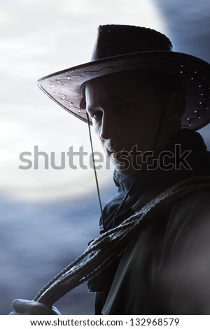 silhouette of Handsome man in cowboy costume stay in steppe at night with full moon. Vampire Hunter - stock photo