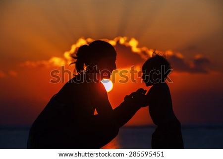 Silhouette of happy beautiful mother smiling to joyful baby boy on sea beach on background of sunset sky with clouds. Motherhood, family lifestyle and summer vacation with child on tropical resort - stock photo