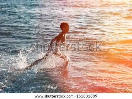 Silhouette of happy boy jumping to the sea at sunset - stock photo