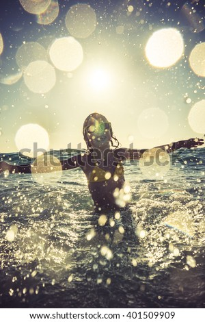 Silhouette of happy child playing in the sea. Kid having fun outdoors. Summer vacation and healthy lifestyle concept. Sunny bokeh. Blurred motion. Toned image - stock photo