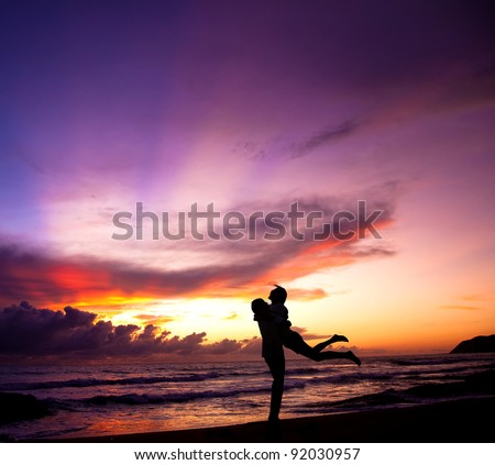 Silhouette of happy  couple embracing on the beach - stock photo