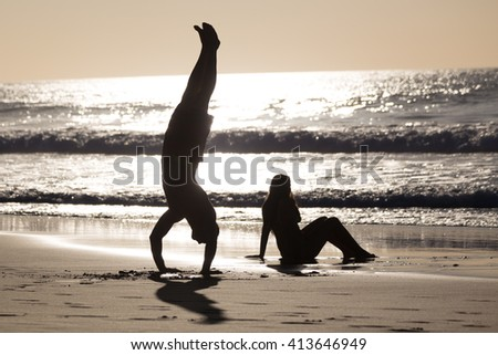 Silhouette of happy couple having fun on beach, man doing headstand. - stock photo