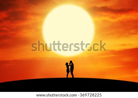 Silhouette of happy couple standing on the hill with the man kissing his girlfriend's hands at sunset time - stock photo
