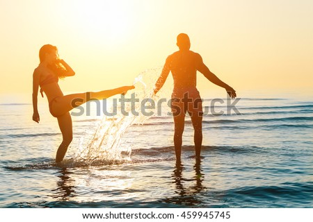 Silhouette of happy couple swimming and playing in water at sunset on beach - Young people having fun on summer time - Vacation and love concept - Focus on him - Sun original color