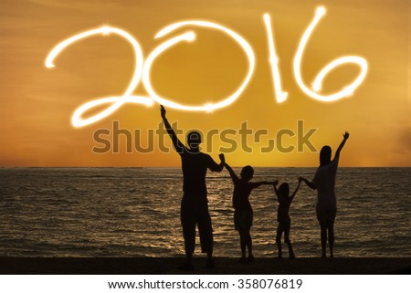 Silhouette of happy family celebrating new year of 2016 on the beach at sunset time - stock photo