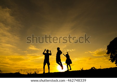 Silhouette of Happy family  jumping at sunset
