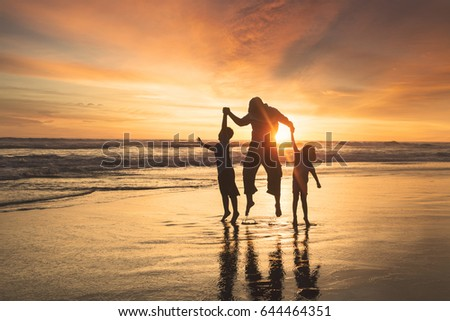 Silhouette of happy family jumping on the beach while holding hands at sunset time