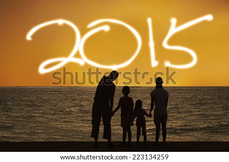 Silhouette of happy family playing on beach and enjoy new year holiday of 2015 - stock photo