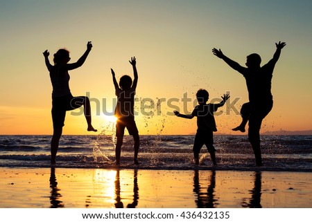 Silhouette of happy family who dancing on the beach at the sunset time. People having fun on the sea. Concept of friendship forever and of summer vacation.