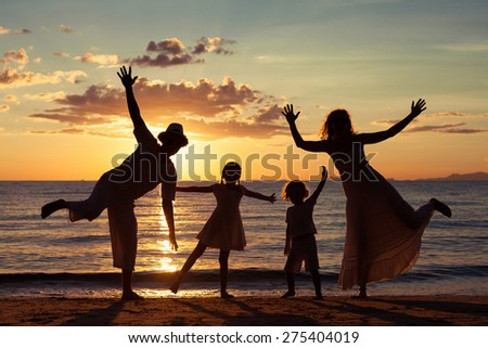 Silhouette of happy family who playing on the beach at the sunset time. Concept of friendly family. - stock photo
