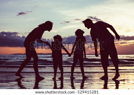 Silhouette of happy family who playing on the beach at the sunset time. People having fun outdoors. Concept of friendly family.
