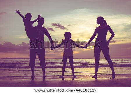 Silhouette of happy family who standing on the beach at the sunset time. People having fun on the sea. Concept of friendship forever and of summer vacation. - stock photo