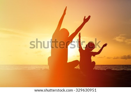 Silhouette of happy father and son at sunset beach - stock photo