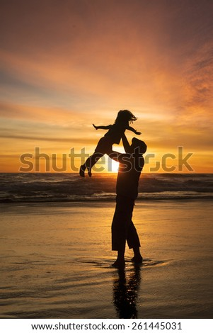 Silhouette of happy father enjoy holiday with his daughter on the beach at sunset time - stock photo