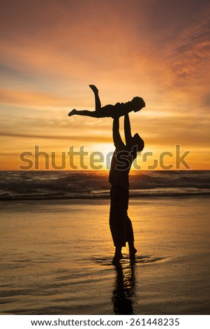 Silhouette of happy father throwing his son on the beach at sunset time - stock photo