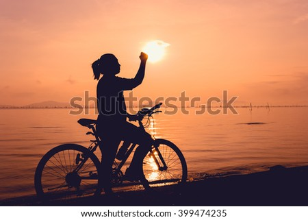 Silhouette of happy female with mountain-bike on colorful orange sky background. Active outdoors lifestyle for healthy concept. Action of winner or successful people.