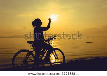 Silhouette of happy female with mountain-bike on colorful yellow sky background. Active outdoors lifestyle for healthy concept. Action of winner or successful people.