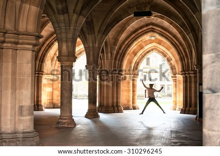 Silhouette of happy girl jumping high up in cloisters of Glasgow University. Scotland. Europe. Summertime outdoors image. - stock photo