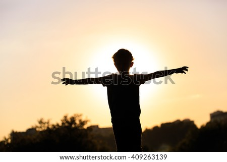 silhouette of happy little boy at sunset