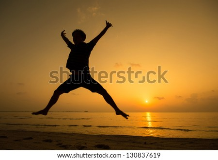silhouette of happy man jumping at the beach.