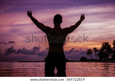 Silhouette of happy man on vacation having fun on the beach of tropical island - stock photo