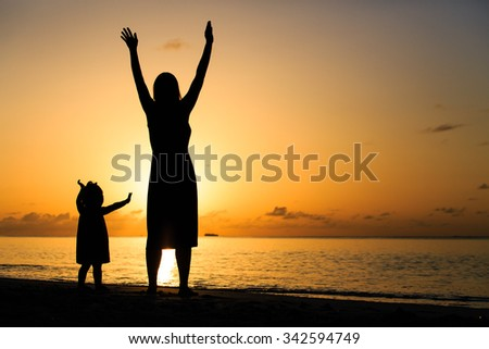 silhouette of happy mother and little daughter hands up at sunset beach