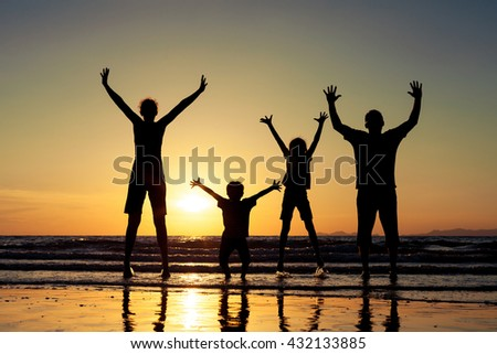Silhouette of happy people. They are standing on the beach at the sunset time. Concept of friendly family.