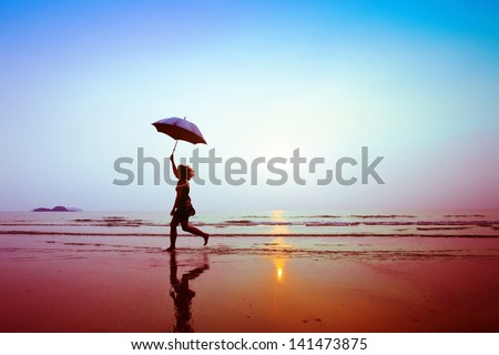 silhouette of happy running woman with umbrella - stock photo