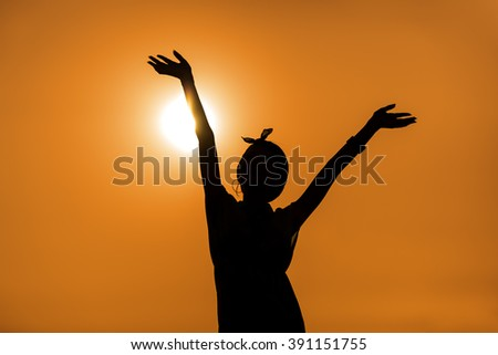 Silhouette of happy woman against sunset