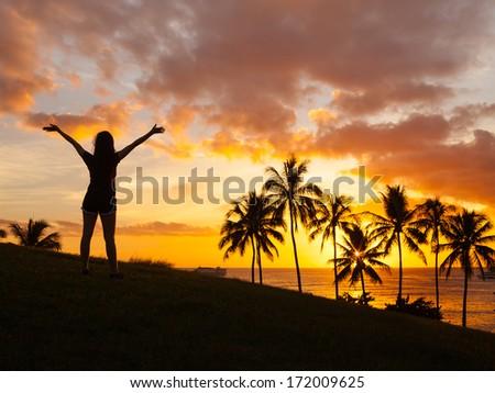 Silhouette of happy woman enjoying beautiful sunset. Freedom concept.  - stock photo