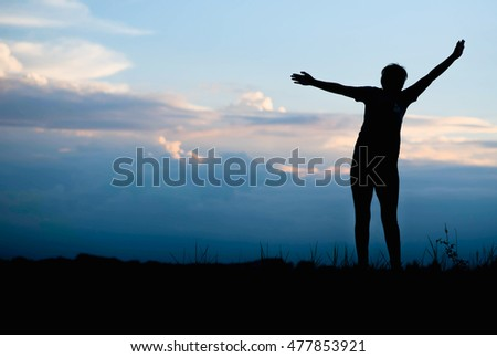 Silhouette of Happy woman jumping in green field against blue sky.