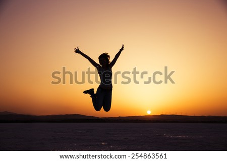 silhouette of happy woman jumping in sunset - stock photo