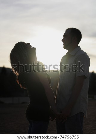silhouette of happy young couple together outdoors - stock photo