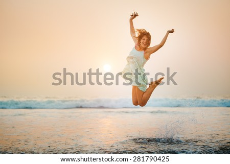 Silhouette of happy young jumping girl - stock photo