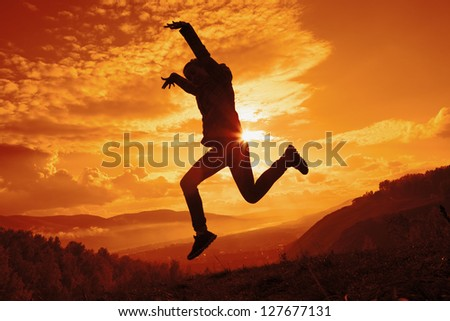 Silhouette of happy young woman jumping at the sunset