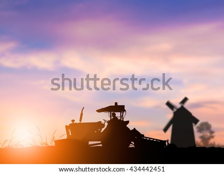 silhouette of heavy machinery working plowed soil in preparation for planting crops. Agriculture is the main industry and the stability of the world. concept food crop. concept to save the world. - stock photo