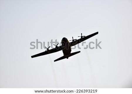 silhouette of hercules transport plane against the blue sky - stock photo