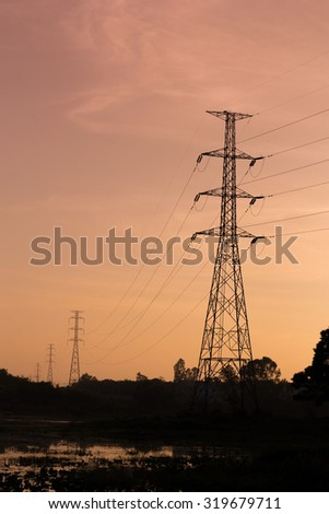 Silhouette of high voltage post at sunset
