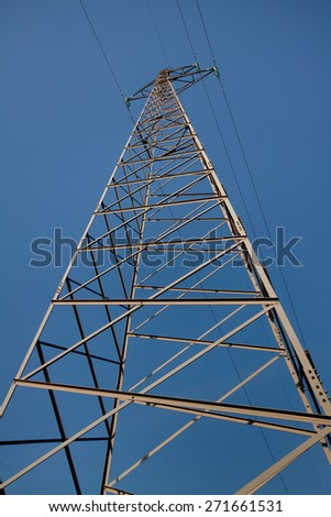 Silhouette of high voltage power transmission lines and pylons at sunset - stock photo