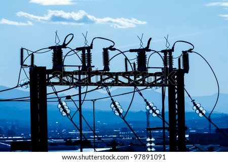 Silhouette of high voltage substation part in an industrial area - stock photo
