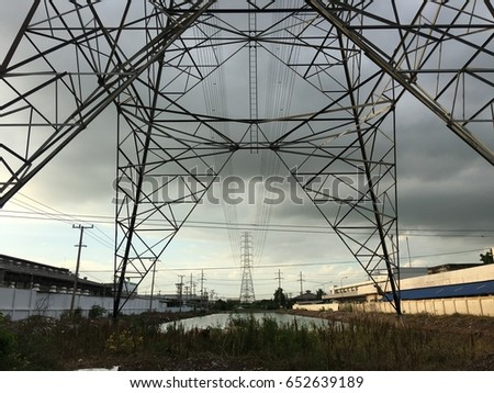 Silhouette of high voltage tower and electric line overcast cloudy sky on day noon light.