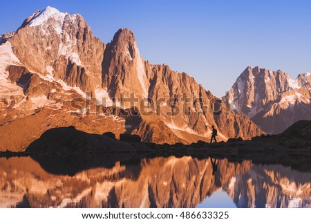 silhouette of hiker traveler with backpack trekking in sunset mountains near the lake