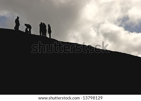 Silhouette of hikers on cliff, rock-climbing, hiking, trekking - lots of copy space - stock photo