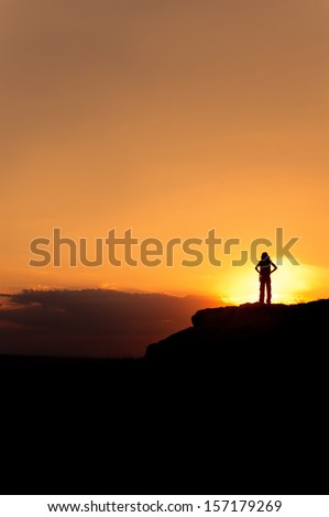 Silhouette of hiking woman with backpack, sunset sky as a background  - stock photo