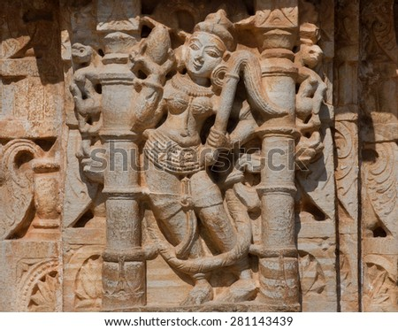 Silhouette of hindu woman on the ancient bas-relief of temple in India - stock photo