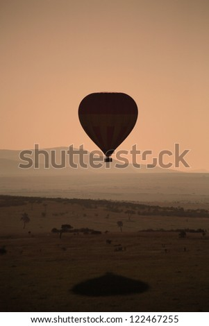 Silhouette of hot air balloon at sunrise over the Masai Mara Kenya Africa - stock photo