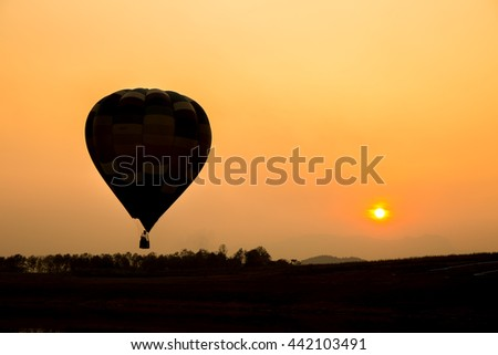 Silhouette of hot air balloon going up in the sky.