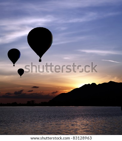 Silhouette of hot air balloons floating up to the sky during a fiery surreal sunset against a mountain at a rural remote seaside. - stock photo